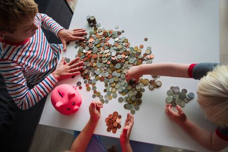 kids count money, boy and girls put coins into piggy bank