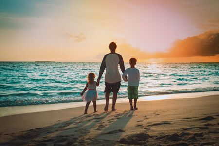 father with son and daughter walking on beach at sunset