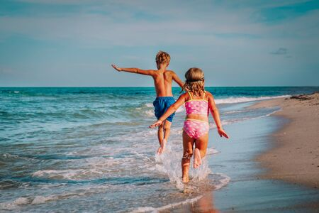little girl and boy run and play with waves on beach Stockfoto