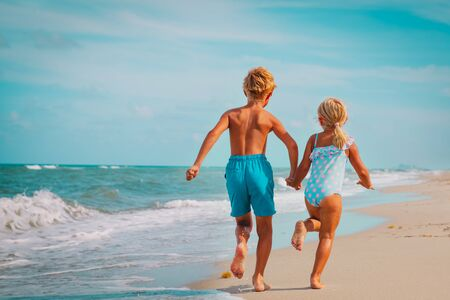happy girl and boy run and play with waves on beach Stockfoto - 133382672