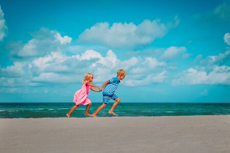 happy girl and boy run on beach, kids enjoy vacation at sea