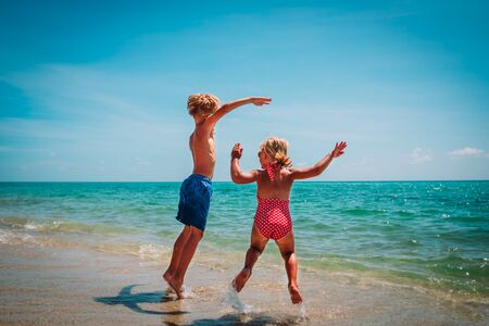 happy little boy and girl play on beach