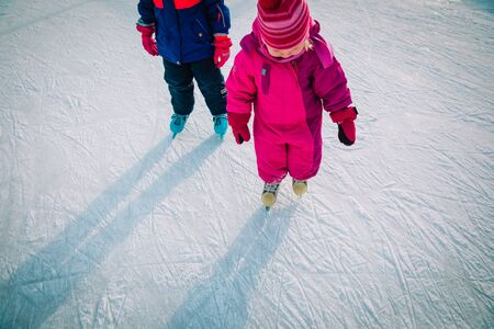little girls skating together in snow, kids winter activities