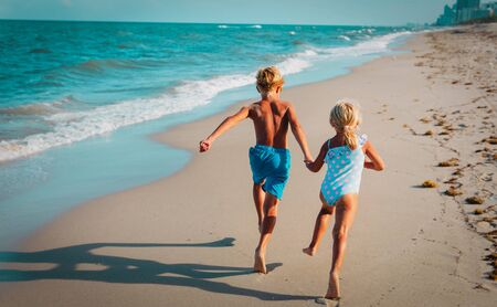happy girl and boy run and play with waves on beach Stockfoto - 133382619