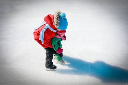 big boy teaching little sister to skate, kids winter sport 版權商用圖片