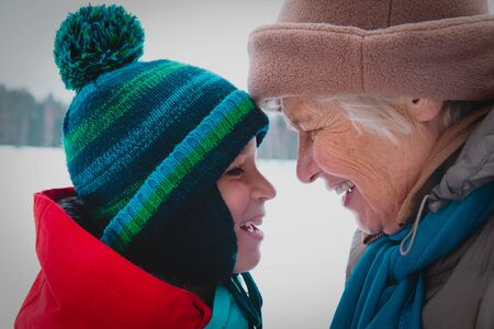 happy grandmother and grandson talk in winter nature