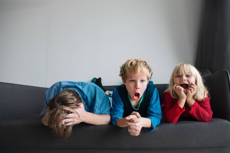 kids shout and make noise while father is stressed and tired Stock Photo