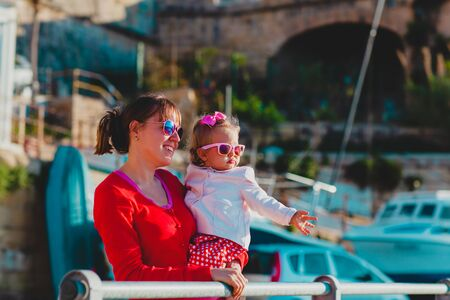happy mother and little daughter travel in quay of Malta