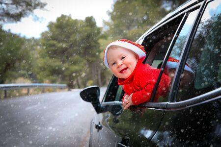 christmas car travel- happy little baby girl loves travel in winter