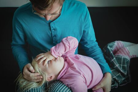 father holding stressed little daughter, sad child, bullying and family support