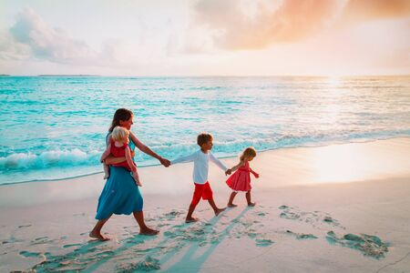 mother and kids walking on beach at sunset, family at sea
