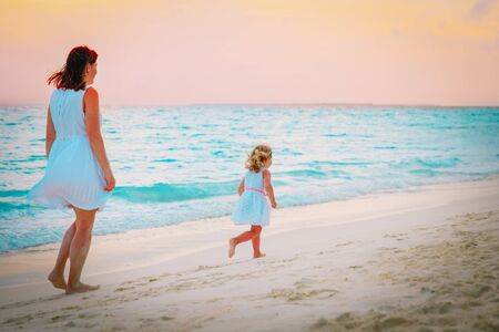mother and little girl walking on beach at sunset, family vacation
