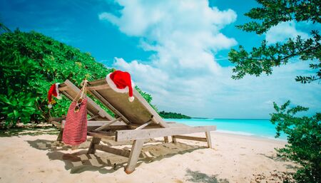 Christmas on beach -chair lounges with Santa hats at sea vacation Stock Photo