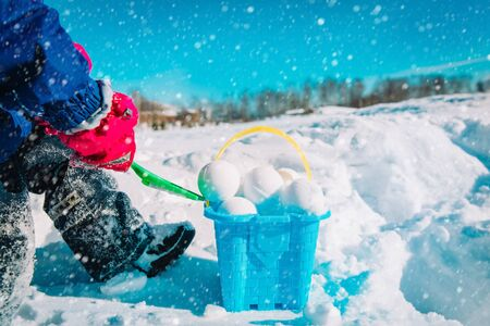 child making snowballs in winter nature, kids play outdoors Stockfoto