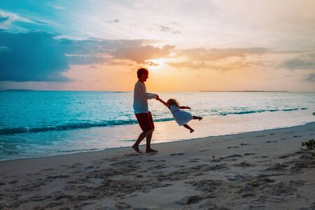 Father and little daughter silhouettes play at sunset beach, family vacation