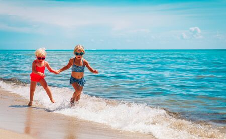 happy cute little girls play with waves on beach, kids enjoy vacation