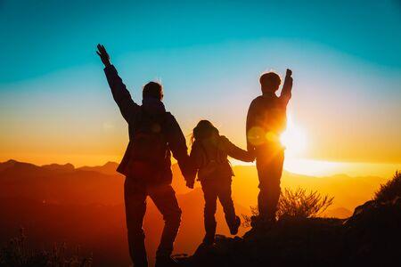 il padre con i bambini viaggia tra le montagne del tramonto, la famiglia felice nella natura