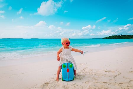 happy cute little girl with luggage and toy plane travel on tropical beach Stock Photo