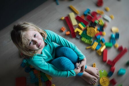 crying little girl with toys at home, kids stress and sadness, child in pain, despair Banco de Imagens