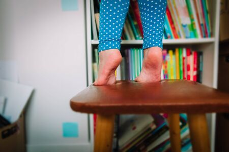 kids safety- little girl climb on chair at home