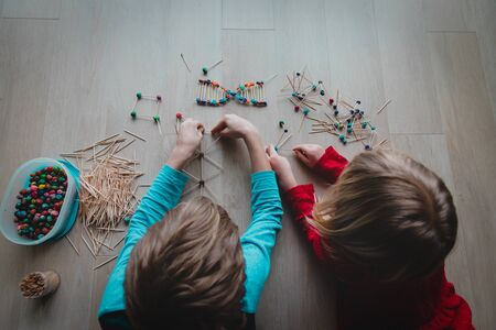 boy and girl making models from sticks and clay, engineering and STEM Stock Photo