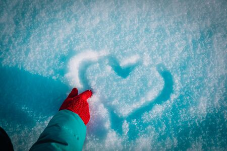 drawing heart on snow, love winter concept, winter nature