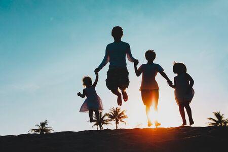 Familia feliz en la playa - padre con hijos saltando de alegría al atardecer Foto de archivo