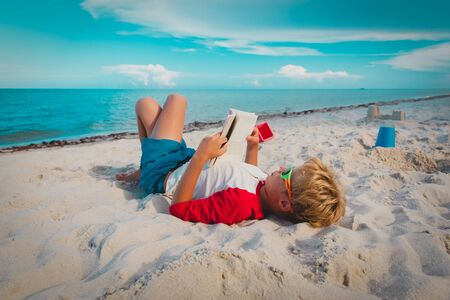 boy reading book at sand beach, kid learning on sea vacation