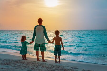 father and kids walking on beach at sunset, family vacation 版權商用圖片