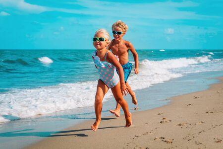 happy boy and girl running on beach