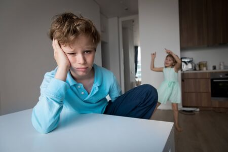 boy feeling anxiety and stress while girl dancing indoors, kid staying home