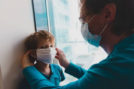father put mask on son before going outside 免版税图像