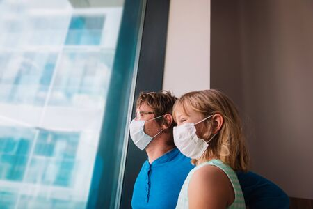 father and daughter in masks looking at the window, family indoors