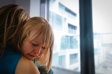 sad crying little girl hugging mother indoors, kids anxiety and stress 免版税图像