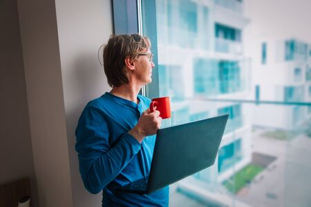 young man looking at window while staying home, remote work during quarantine