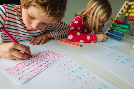 boy and girl writing numbers, kids doing homework