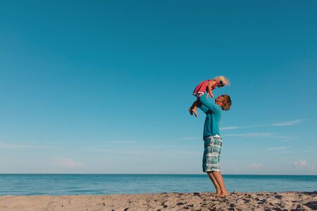 father and little daughter play at sky on beach