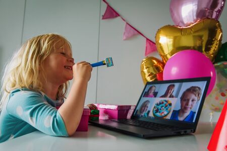 Happy little girl celebrating birthday at home with family on video call