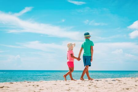 little boy and girl walk on summer beach