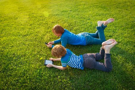 father and son with book and mobile phone on grass