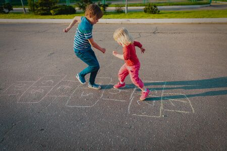 kids playing hopscotch outside, boy and girl have fun