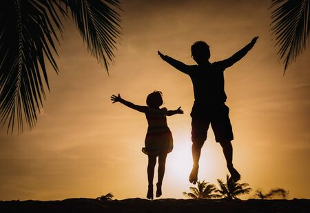 happy father and daughter silhouettes play on beach at sunset