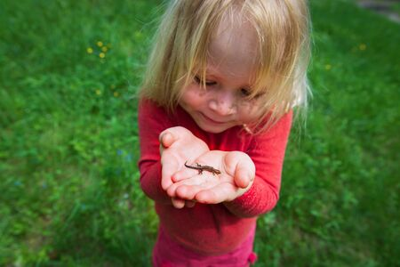 little girl holding and exploring lizard in nature