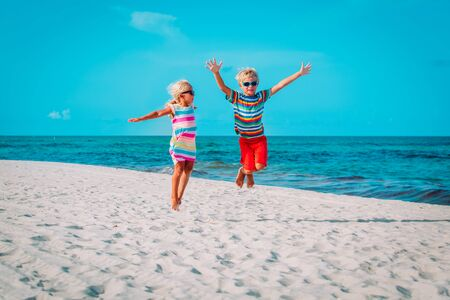 happy little boy and girl play on beach, kids enjoy tropical vacation Stok Fotoğraf