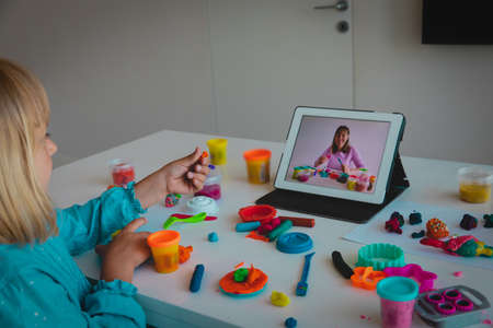 Child play with clay molding shapes during online lesson