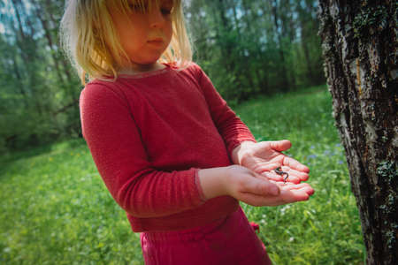 little girl holding and looking at lizard in nature