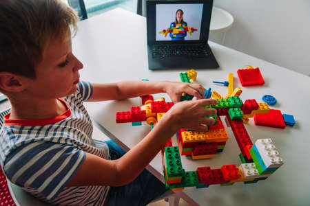 kid building project with constructor during online lesson. Remote learning.
