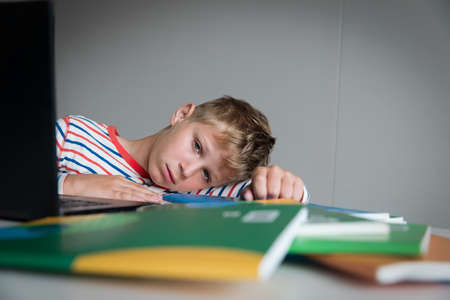 Child tired and bored of doing homework