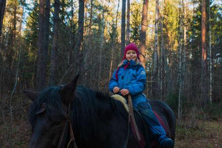 happy little girl on horse ride in forest Foto de archivo