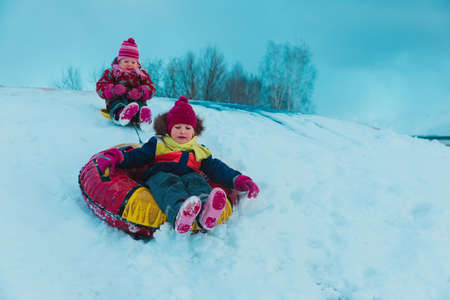 happy little girls slide in winter snow Standard-Bild